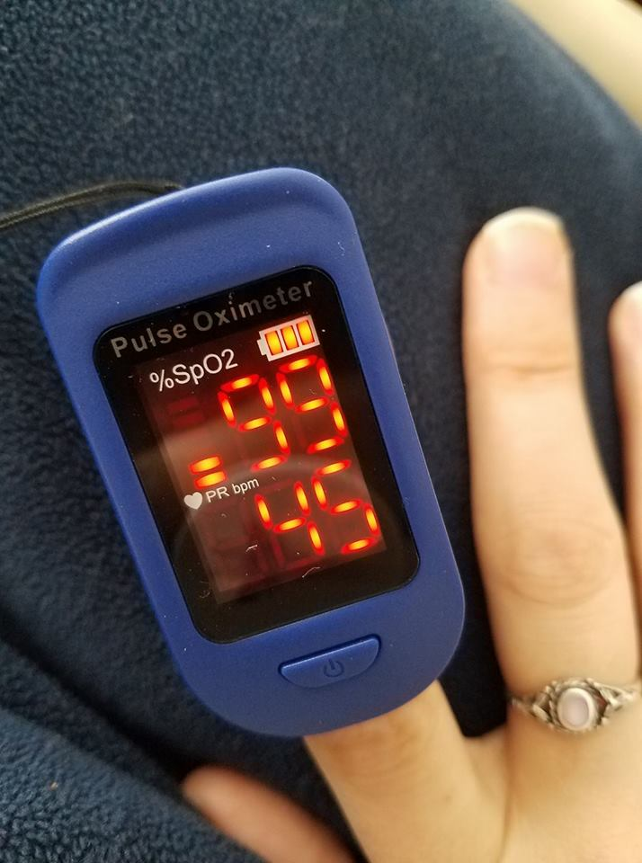 woman wearing a pulse monitor on her finger