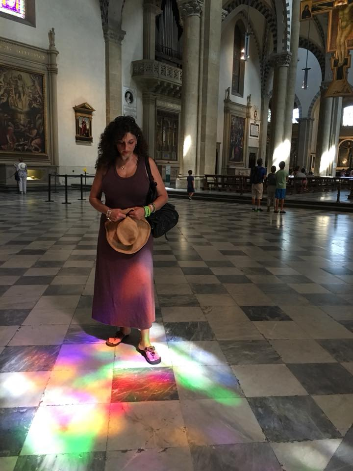 woman standing indoors looking at a rainbow of light reflected on the floor