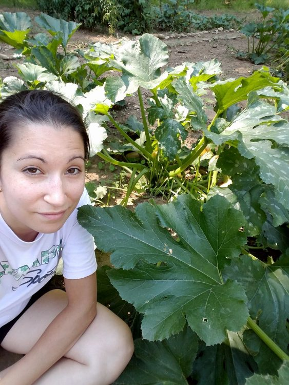 woman kneeling next to plants