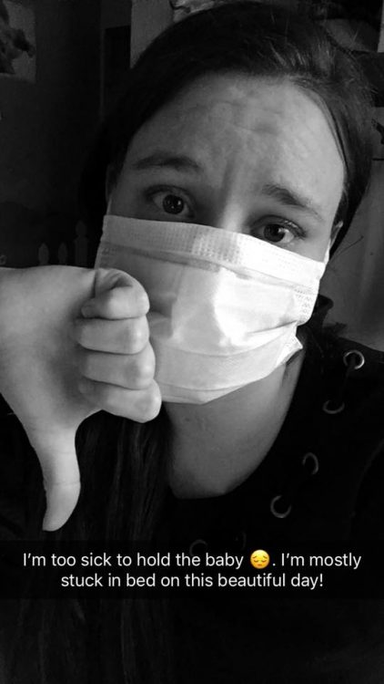girl wearing surgical mask giving thumbs down