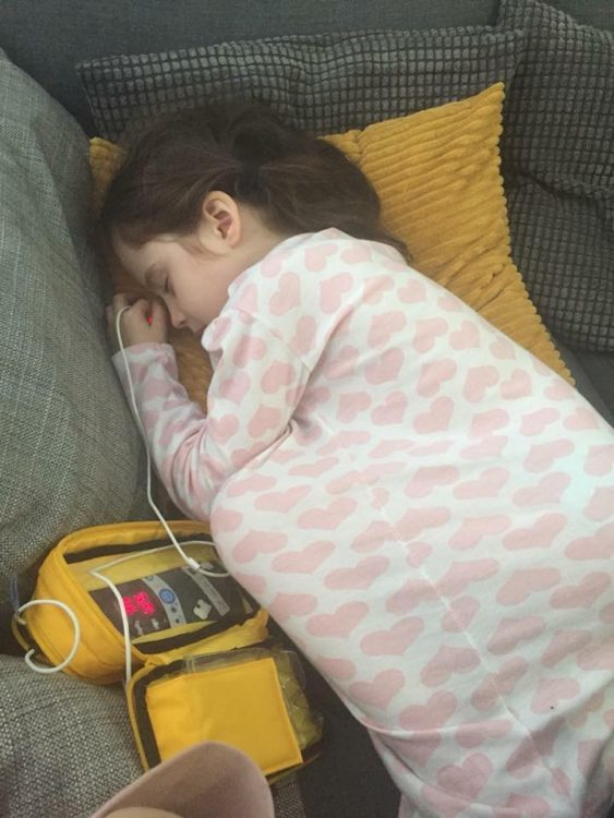 Donna's daughter lying on the couch attached to medical equipment