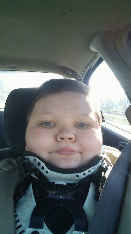 author's son with a neck brace in the car