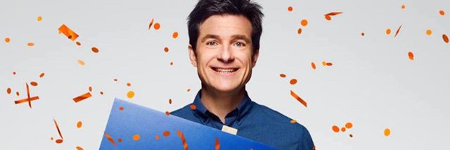 """Jason Bateman holding a sign that says, """"Bluth for family of the year"""""""