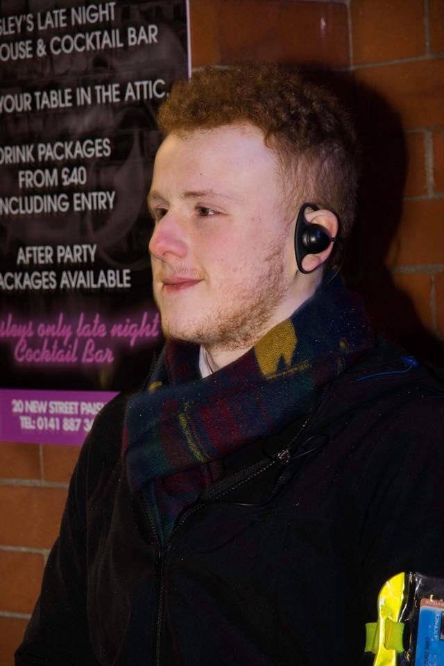 man wearing a black jacket and earpiece standing outside as a bouncer