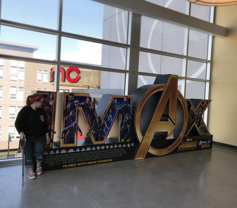 woman standing in front of an Avengers sign at a movie theater with her cane