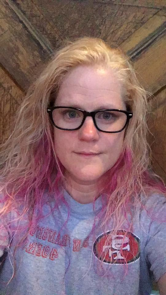 woman with pink hair and glasses taking a selfie