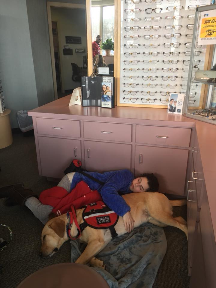 woman lying on the floor of a waiting room with her service dog