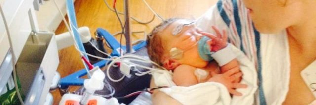 Mother holding baby in NICU, baby has many wires