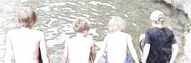 Boys sitting by a lake.