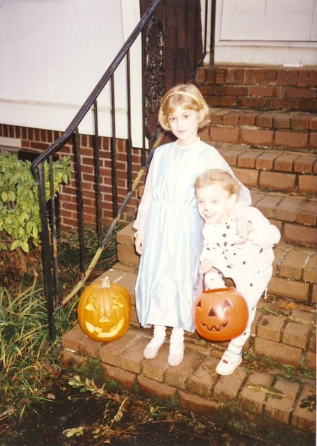 Julia and her younger brother during Halloween, standing on steps