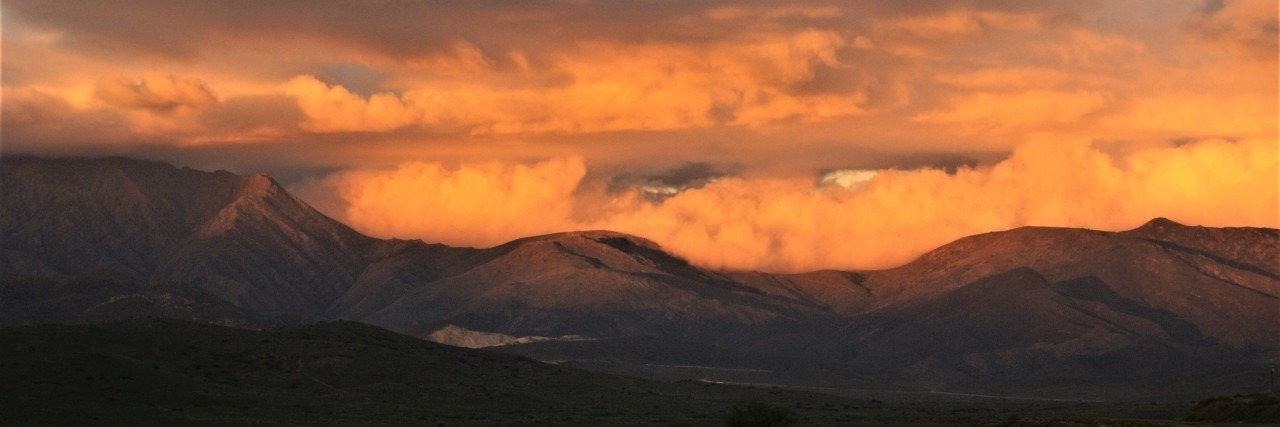 mountains covered by orange clouds at sunset