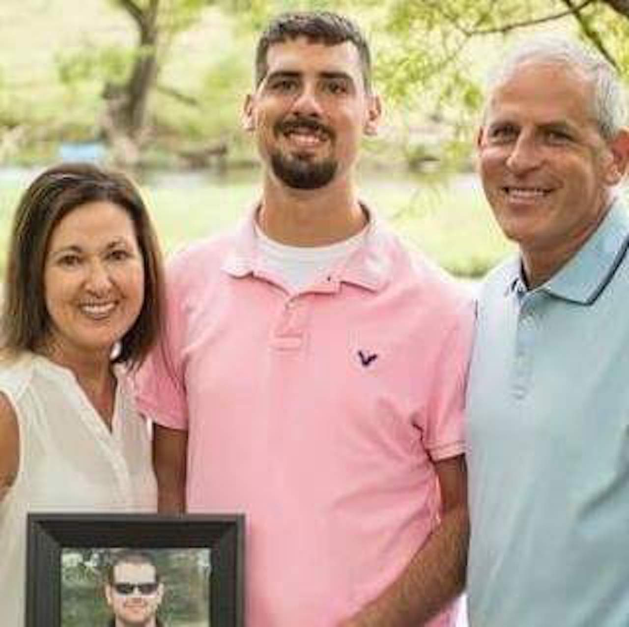 mom son and dad holding picture of sibling