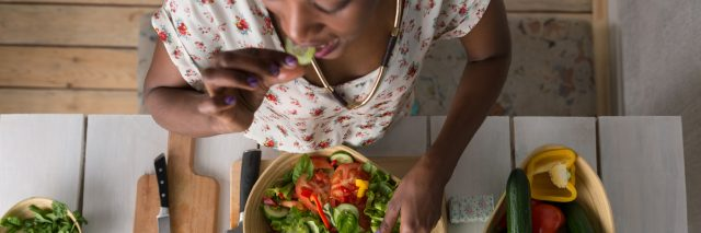 An African American woman eating a salad at a table, with the camera looking down at her.