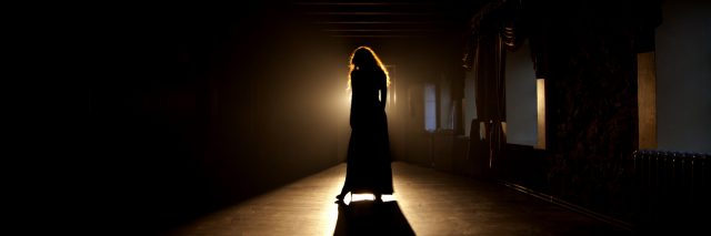 Woman in shadows on stage.
