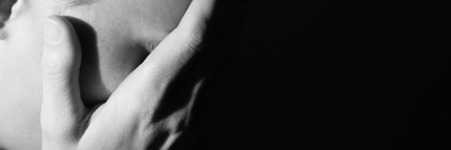 black and white photo of a woman holding her head in her hands
