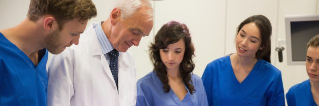 Medical students and professor examining patient.