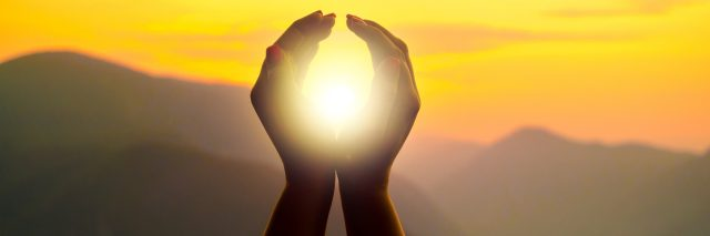 Woman's hands circling the sun, during a sunset in the mountains.