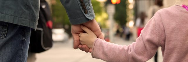 Father holding child's hand.