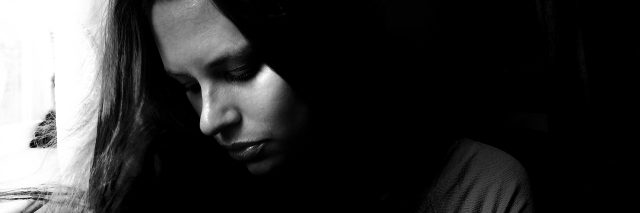 black and white portrait of young woman looking away in sadness and depression