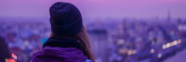 Hipster girl traveler with backpack looking at winter evening cityscape, purple violet sky and blurred city lights