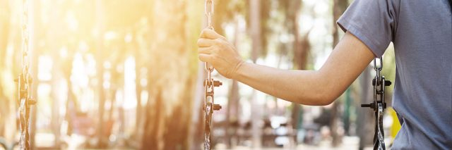 Lonely woman swinging in the park reaching and holding empty swing next to her