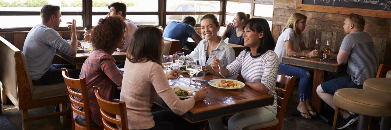 Four female friends at lunch in busy restaurant