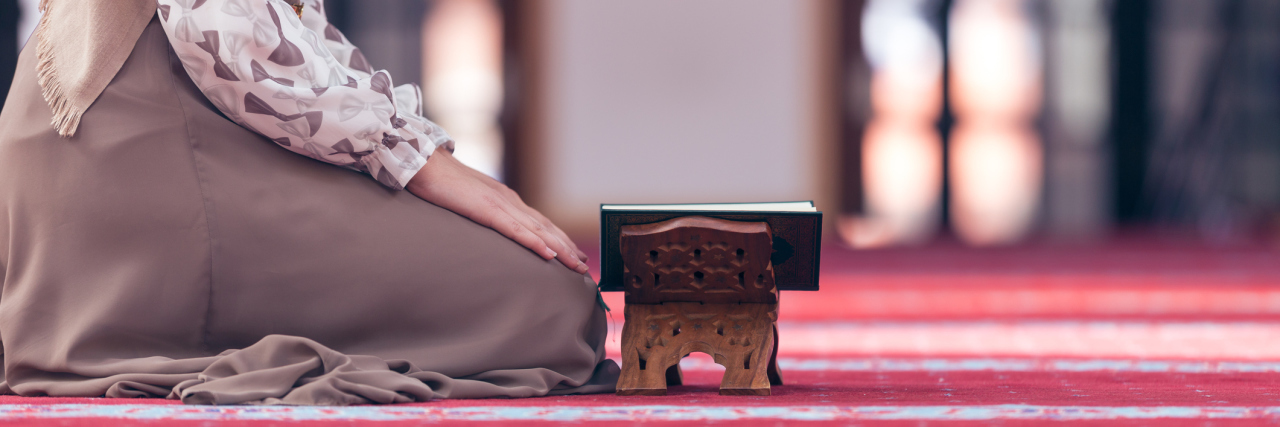 A picture of a Muslim woman kneeling on the ground, reading her Quran.