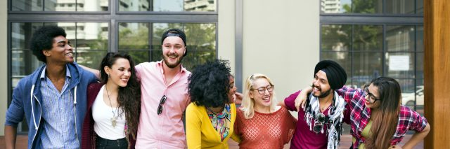 College students of varied ethic backgrounds linking arms, smiling and laughing.