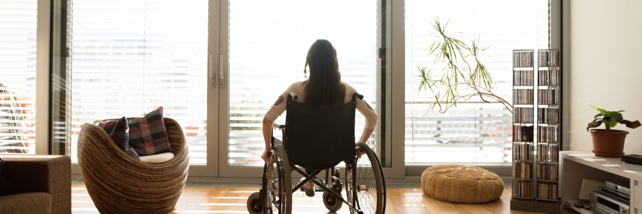 Disabled woman in wheelchair at the window at home.