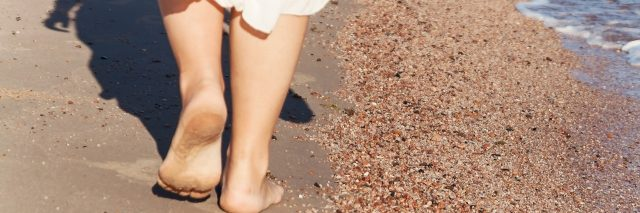 vacation travel - woman leg closeup walking on white sand relaxing in beach cover-up pareo beachwear.