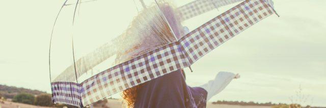 Woman carrying a solar umbrella in a field