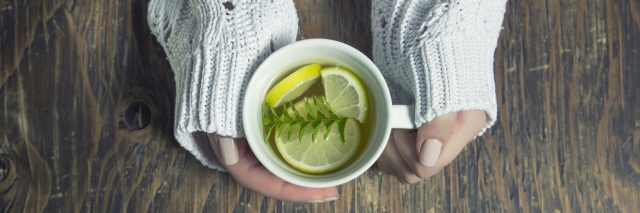 A woman holding a coffee mug, with tea inside it - as well as thyme herb, and lemon slices.
