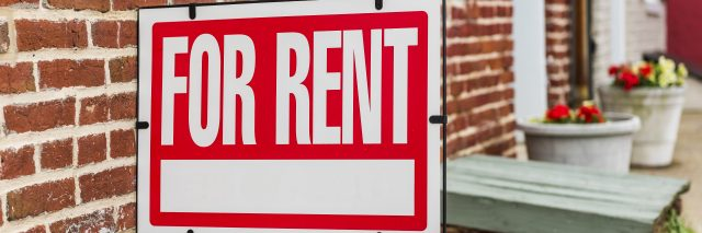 Red For Rent sign closeup against brick building.