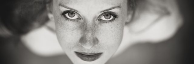 A black and white picture of a woman, the camera looking down on her face.