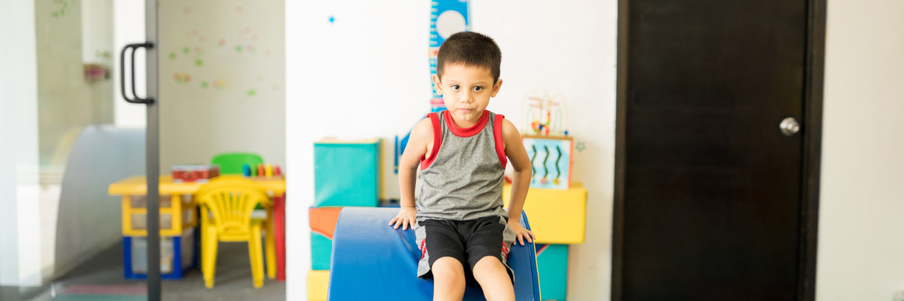 Portrait of a Hispanic boy having fun in a therapy room and going through and obstacle course in a children therapy center