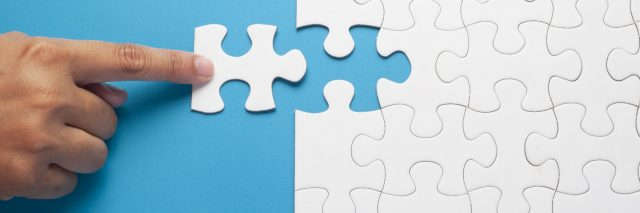 white puzzle pieces being joined against blue background