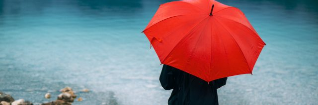 Woman with red umbrella contemplates on rain in front of a lake.