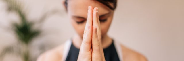 woman with her hands pressed together breathing and meditating