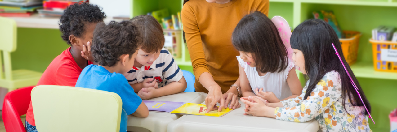 Asian female teacher teaching mixed race kids reading book in classroom,Kindergarten pre school concept