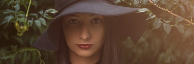 A woman standing outside, in front of a tree, wearing a black sunhat and a serious expression.