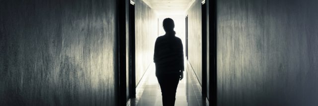 woman walking down dark hallway towards light