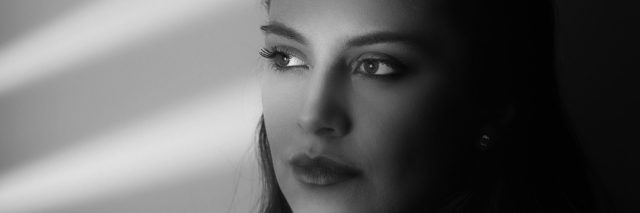 A black and white image of a woman looking out a window, only showing the shutter shadows across the wall and across her face.