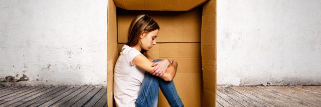 woman sitting inside a cardboard box