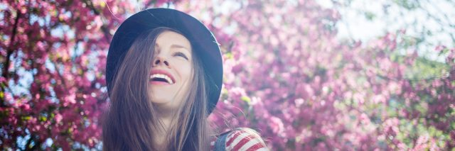 woman wearing a hat and striped shirt laughing under a cherry blossom tree