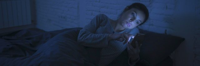 woman lying in bed looking at her phone
