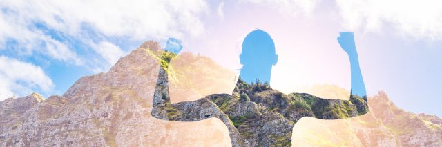 Silhouette of woman against mountains.