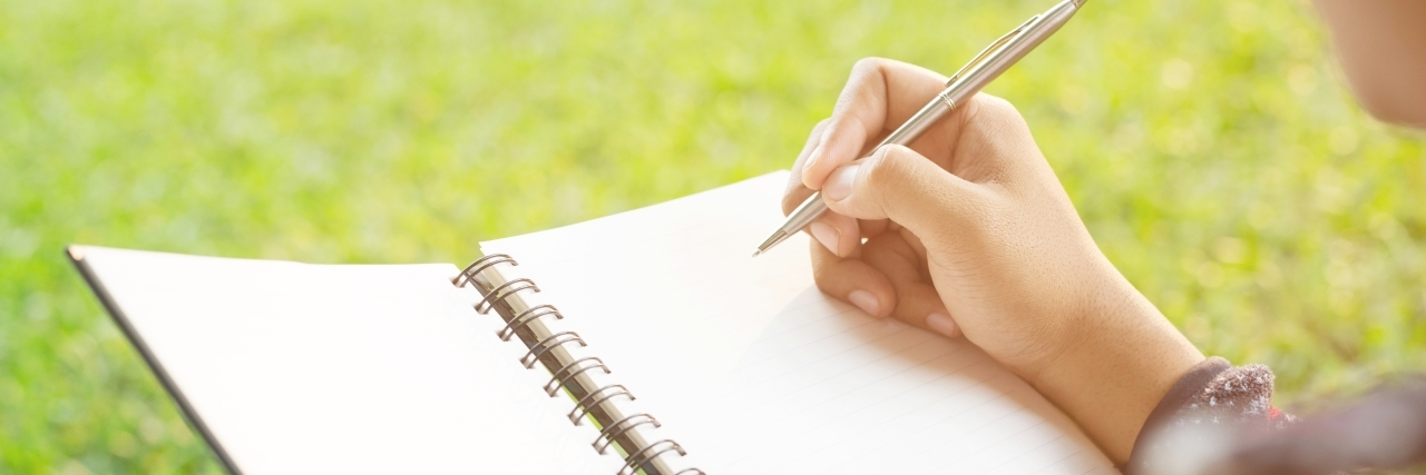close up of someone writing in a notebook on the grass