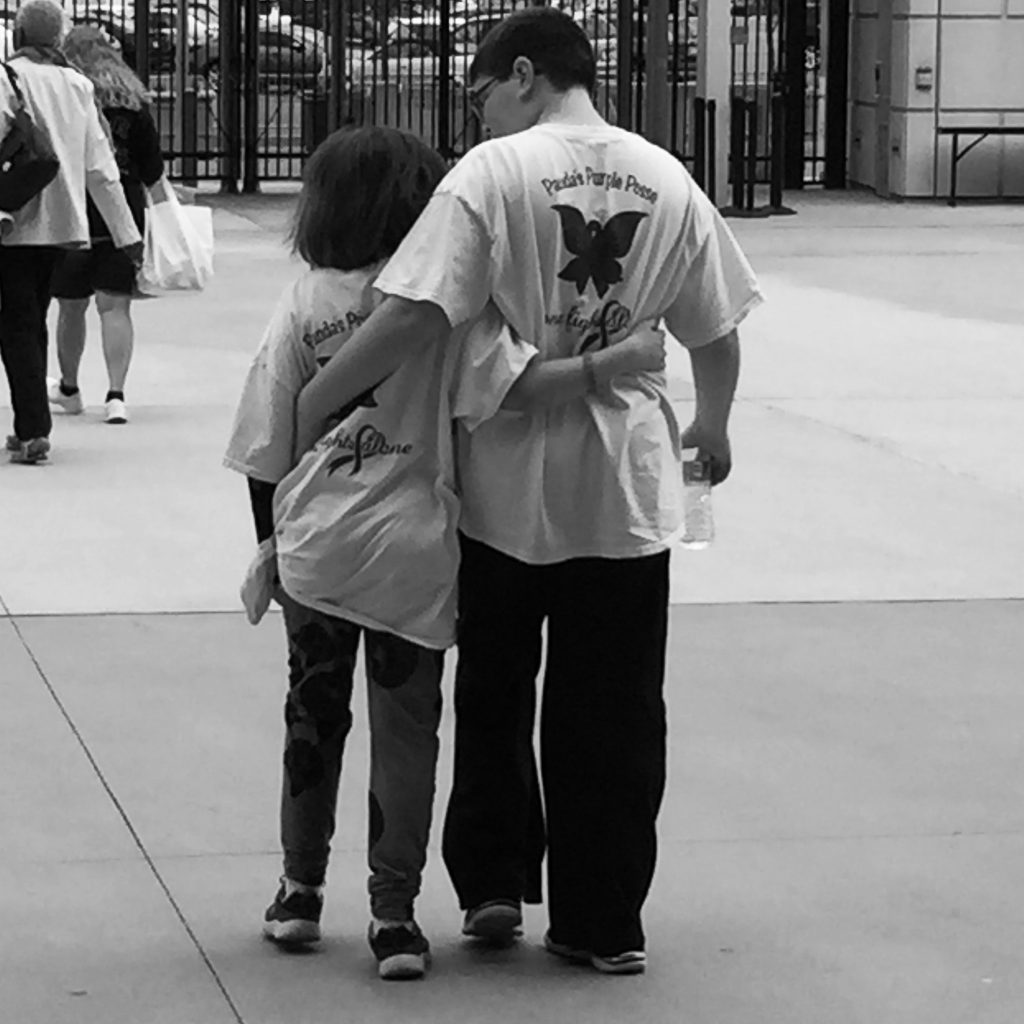 black and white photo of two people walking side by side and hugging
