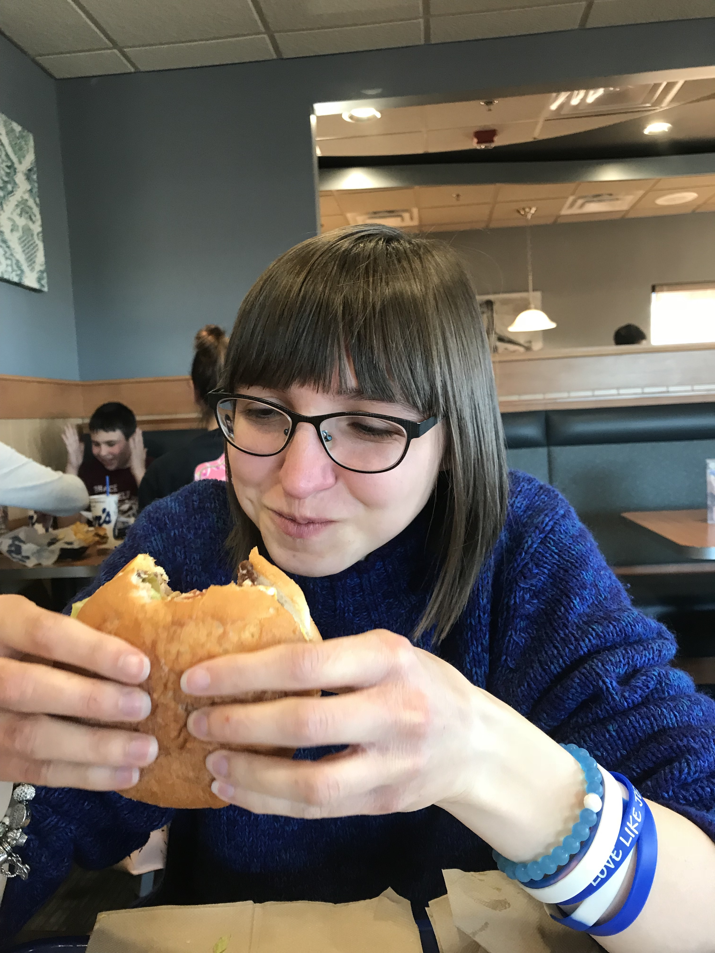 A picture of the writer looking at a cheese burger, with one bite already taken out.