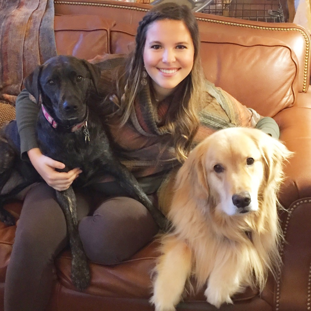 woman sitting on the couch smiling with two dogs